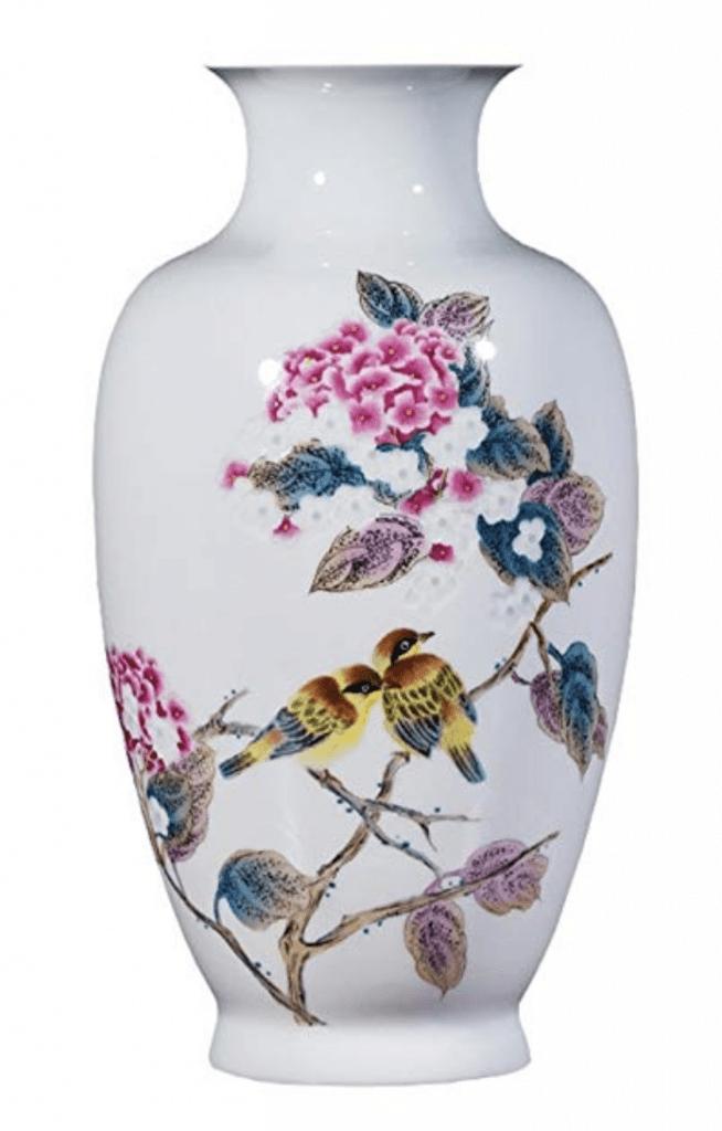 Jarrón blanco de pequeños pájaros con flores rosas